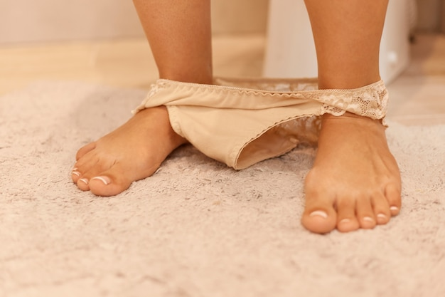 Afbeelding van de blote benen en voeten van een vrouw met haar beige slipje liggend op de badkamervloer rond haar enkels, vrouw staande in de buurt van toilet op zacht tapijt.
