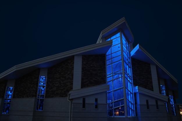 Afbeelding van de buitenkant van de kapel met grote ramen, 's nachts blauw verlicht