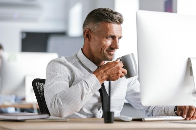 Afbeelding van de gelukkige zakenman 30s dragen witte overhemd en stropdas thee drinken uit beker, zittend door de computer op kantoor