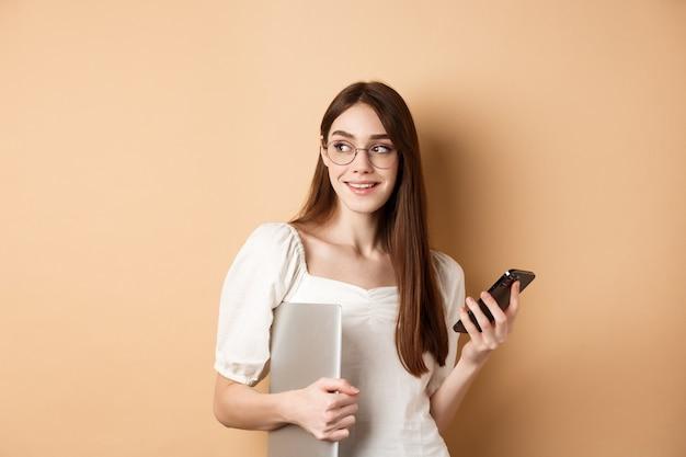Afbeelding van de jonge stijlvolle vrouw aan het werk, met laptop en smartphone, opzij kijken naar lege ruimte, staande op beige achtergrond.
