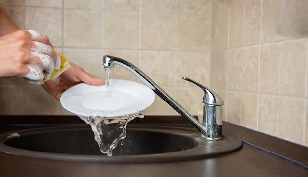 Afbeelding van de kant van iemands handen transparante mok in de gootsteen in de keuken wassen