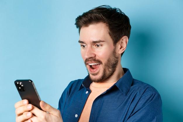 Afbeelding van de knappe jongeman die zich gelukkig voelt bij het lezen van goed nieuws op de mobiele telefoon, vrolijk staande tegen een blauwe achtergrond.