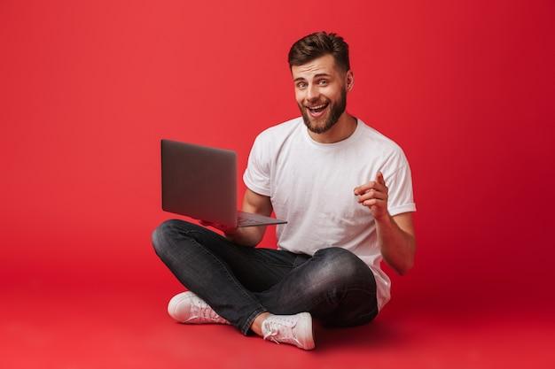 Afbeelding van de knappe man in t-shirt en spijkerbroek zittend op de vloer met gekruiste benen en wijsvinger wijzend naar de camera, wat betekent dat je een laptop vasthoudt, geïsoleerd op rode achtergrond