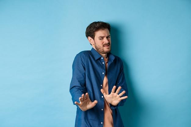 Afbeelding van de man ineenkrimpen en naar iets walgelijks kijken, een stap terug doen van vreselijk ding en het blokkeren met handen, staande op een blauwe achtergrond. kopieer ruimte