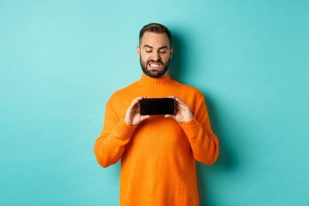 Afbeelding van de man ineenkrimpen naar iets op het mobiele scherm, walgend starend naar het display, smartphone tonen, staande over de lichtblauwe achtergrond.