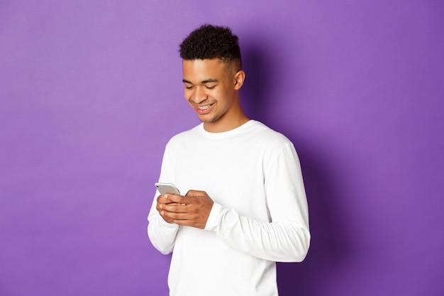 Afbeelding van de moderne jongeman met behulp van smartphone, scherm kijken en glimlachen, permanent over paars.
