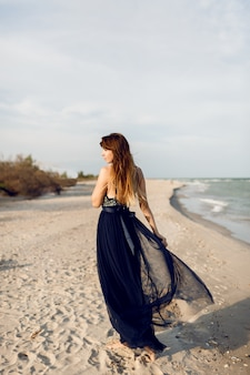 Afbeelding van de volledige hoogte van modieuze vrouw in elegante luxe jurk poseren op het strand. uitzicht vanaf de achterkant. lange haren.