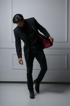 Afbeelding van de volledige lengte van een elegante mode-man die zijn pak aanpast terwijl hij naar beneden kijkt, weg van de camera, op een witte achtergrond. verticale weergave.