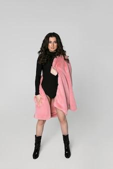 Afbeelding van de volledige lengte van een prachtig vrouwelijk model met lang donkerbruin krullend haar in zwarte bodysuit en fut coat, geïsoleerde witte achtergrond. verticale weergave.