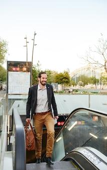 Afbeelding van de volledige lengte van een volwassen zakenman in stijlvolle formele kleding, naar boven gaan van metro op roltrap in het centrum met mannelijke leerzak en krant in handen