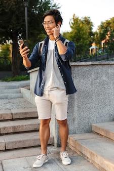 Afbeelding van de volledige lengte van gelukkige aziatische mannelijke student in brillen praten door video-oproep op smartphone buitenshuis