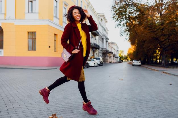 Afbeelding van de volledige lengte van jonge dame in hoed en wollen jas springen