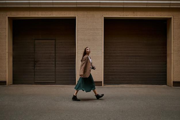 Afbeelding van de volledige lengte van modieuze jonge vrouw met breed haar die tegen de deuren van rolluiken stapt, gaat werken, met een ernstige gezichtsuitdrukking