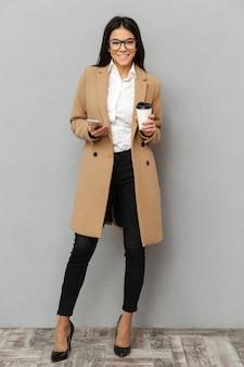Afbeelding van de volledige lengte van mooie vrouw dragen bovenkleding staande bedrijf met mobiele telefoon en afhaalmaaltijden koffie in handen, geïsoleerd over grijze achtergrond