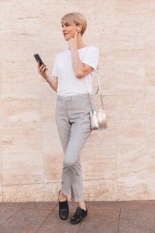 Afbeelding van de volledige lengte van stijlvolle blonde vrouw, gekleed in een wit t-shirt met behulp van mobiele telefoon, terwijl staande tegen een beige muur buiten en bluetooth oortelefoon aan te raken