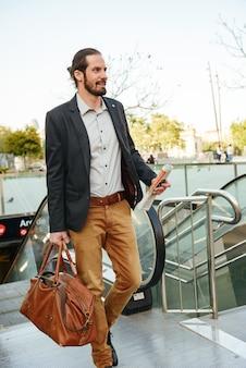 Afbeelding van de volledige lengte van succesvolle zakenman in stijlvolle formele kleding, de roltrap in het centrum opgaan met mannelijke leerzak en krant in handen