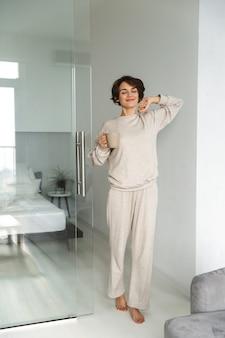 Afbeelding van de volledige lengte van vrolijke brunette vrouw wakker en koffie drinken in de ochtend