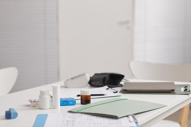 Afbeelding van de werkplek van de arts met medicijnen op de medische kaart en andere benodigdheden erop in het ziekenhuis