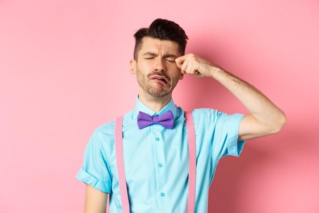 Afbeelding van diepbedroefde man huilen en afvegen van het gezicht, snikken en zich verdrietig of eenzaam voelen, boos op roze achtergrond staan.
