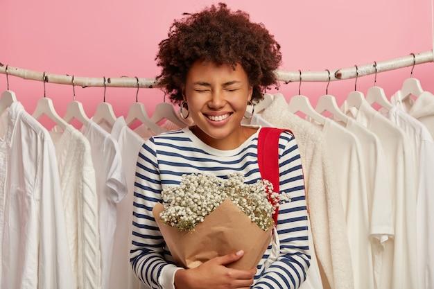 Afbeelding van dolblij gekrulde harige vrouw in gestreepte trui, besteedt vrije tijd in kledingwinkel
