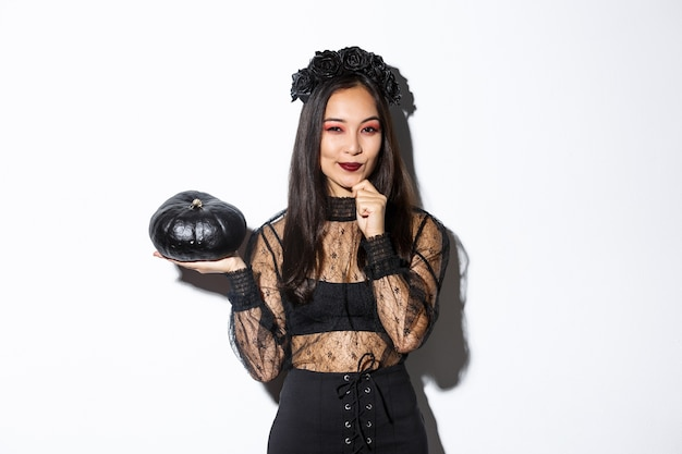 Afbeelding van doordachte lachende aziatische heks, meisje in halloween kostuum camera kijken en zwarte pompoen tonen.