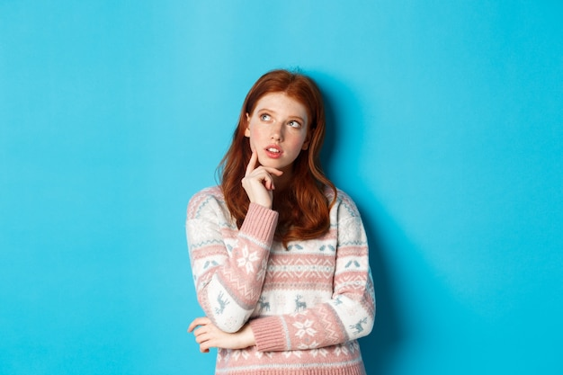 Afbeelding van doordachte roodharige meisje kijkt naar de linkerbovenhoek, denkt of maakt een keuze, staande in de winter trui op blauwe achtergrond.
