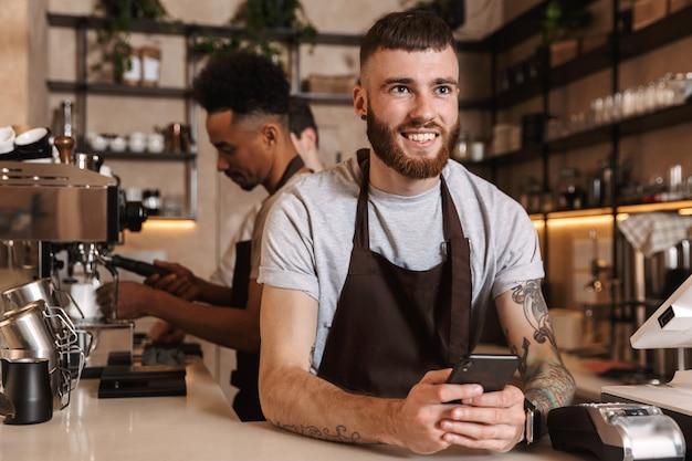 Afbeelding van drie gelukkige koffiemannen-collega's in café-bar die binnenshuis werken met behulp van mobiele telefoon.