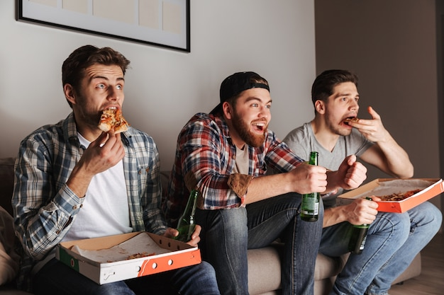 Afbeelding van drie jonge vrijgezellen die met plezier pizza eten, terwijl ze thuis tv kijken naar een voetbalwedstrijd