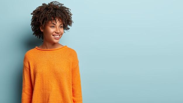 Afbeelding van dromerige vrouw met knapperig haar kijkt peinzend opzij, heeft een zachte glimlach op het gezicht, draagt een oranje trui, stelt zich iets aangenaams voor, modellen over blauwe muur, lege ruimte voor promotie
