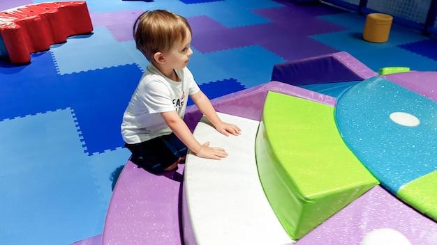 Afbeelding van een 3 jaar oude peuterjongen die klimt en kruipt op de kindergrond in het winkelcentrum. er zijn veel zachte matten voor de veiligheid van kinderen