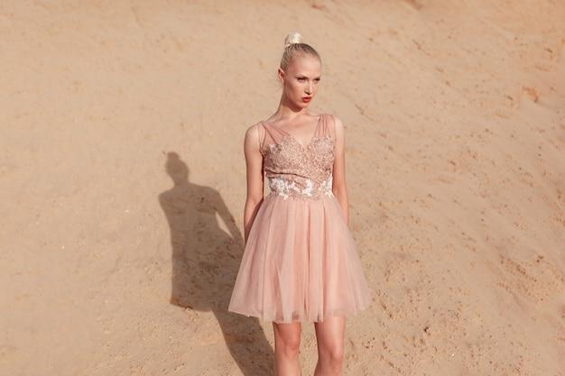 Afbeelding van een aantrekkelijke blonde jonge vrouw die zich voordeed in een borduurjurk die zich voordeed in de woestijn, kijkend naar de zijkant.