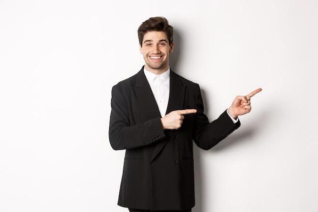 Afbeelding van een aantrekkelijke glimlachende man gekleed voor nieuwjaarsfeest, met de vingers naar rechts wijzend en advertenties tonend, staande op een witte achtergrond