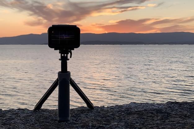 Afbeelding van een actiecamera op een statief die de zonsondergang over de oceaan close-up fotografeert