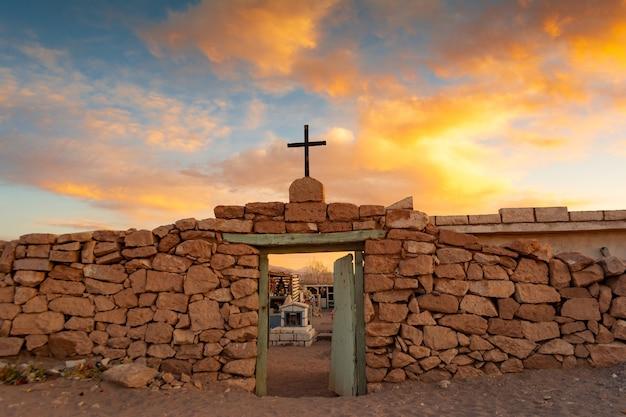 Afbeelding van een antieke poort met een kruis onder de grote hemel