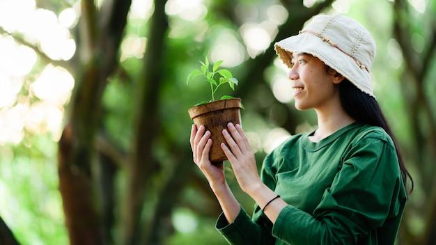 Afbeelding van een aziatische vrouw in het concept van het planten van bomen voor het milieu Premium Foto
