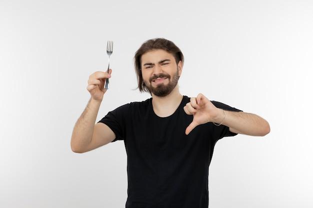 Afbeelding van een bebaarde man met vork en duim omlaag.