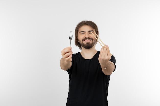 Afbeelding van een bebaarde man met vork over een witte muur.