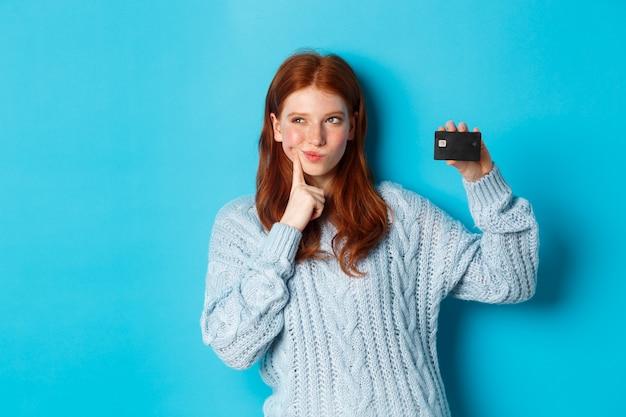 Afbeelding van een bedachtzaam roodharig meisje dat nadenkt over winkelen, creditcard toont en nadenkt, staande over een blauwe achtergrond.