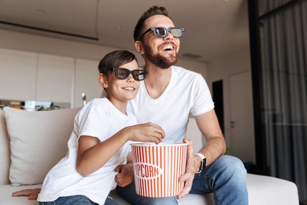 Afbeelding van een blanke vader en zoon die een 3d-bril draagt die popcorn eet en lacht, zittend op de bank thuis en film kijken