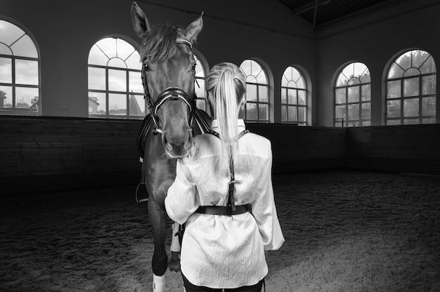 Afbeelding van een blonde vrouw in de vorm van een ruiter vanaf de achterkant. paardenrennen en paardensport concept. gemengde media