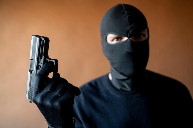 Afbeelding van een dief met bivakmuts en pistool in de hand