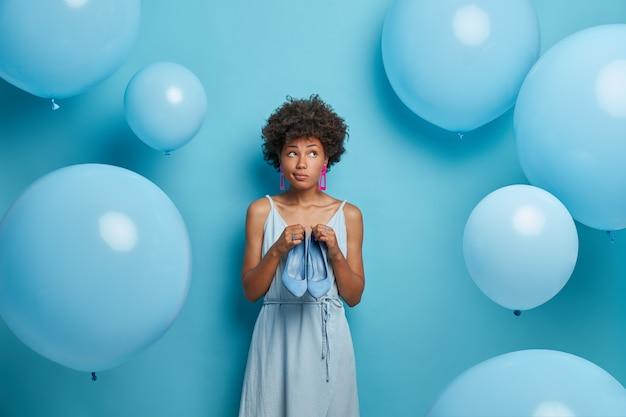 Afbeelding van een doordachte vrouw met afro-haarjurken voor een feestje, denkt wat beter te dragen is, draagt een blauwe jurk en houdt schoenen met hakken vast, wacht op iets speciaals, poseert tegen opgeblazen luchtballonnen