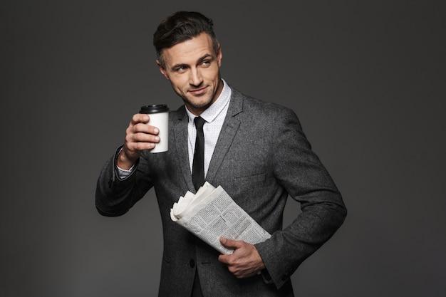 Afbeelding van een drukke zakelijke man gekleed in een zakelijk kostuum opzij kijken en afhaalkoffie drinken met de krant in de hand, geïsoleerd over grijze muur