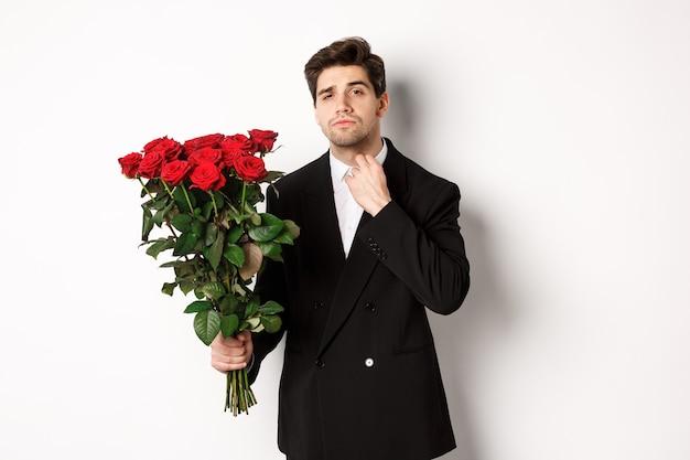 Afbeelding van een elegante en brutale man in een zwart pak, die er zelfverzekerd uitziet en een boeket rode rozen vasthoudt, op een romantische date gaat, staande tegen een witte achtergrond.