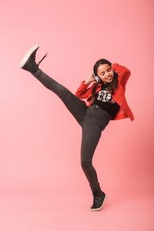 Afbeelding van een energiek meisje in casual dragen koptelefoon dansen terwijl u luistert naar muziek, geïsoleerd over rode muur