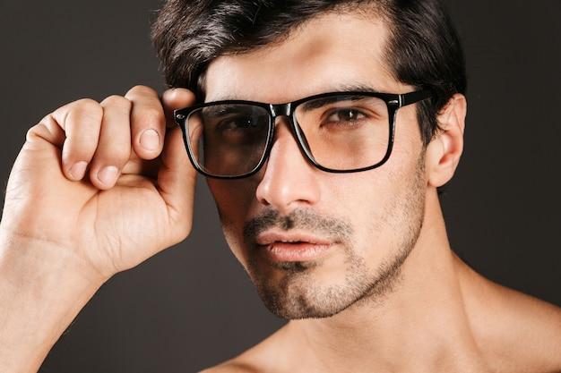 Afbeelding van een ernstige geconcentreerde knappe jongeman geïsoleerd met een bril.