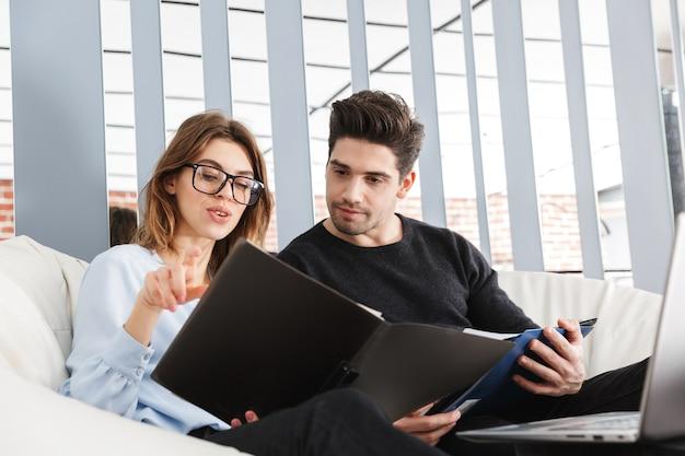 Afbeelding van een geconcentreerde jonge verliefde paar thuis binnenshuis met behulp van laptop computer werken met documenten.
