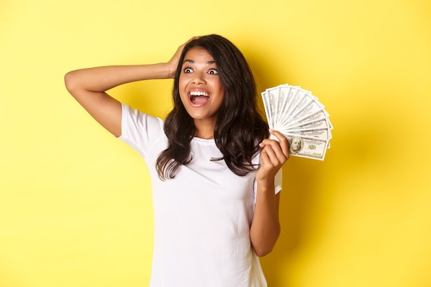 Afbeelding van een gelukkig afrikaans-amerikaans meisje dat opgewonden kijkt in de linkerbovenhoek en geld vasthoudt