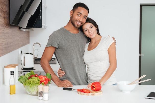 Afbeelding van een gelukkig jong stel in de keuken knuffelen tijdens het koken. voorkant kijken.
