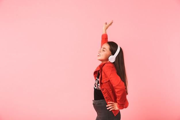 Afbeelding van een gelukkig klein meisje in casual dragen koptelefoon dansen tijdens het luisteren naar muziek, geïsoleerd over rode muur
